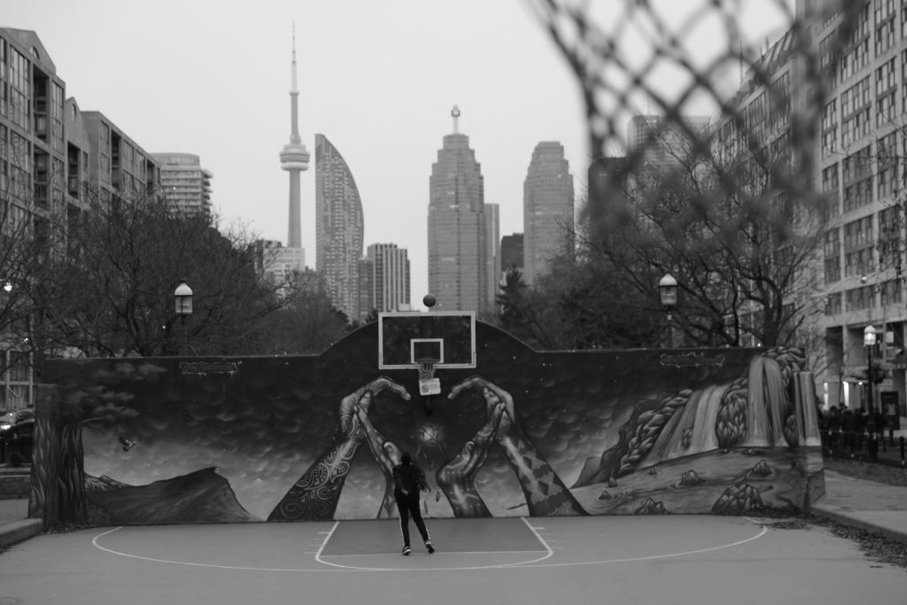 A boy shoots a basketball with the Toronto skyline behind him at David Crombie Park. Photography by Luke Galati