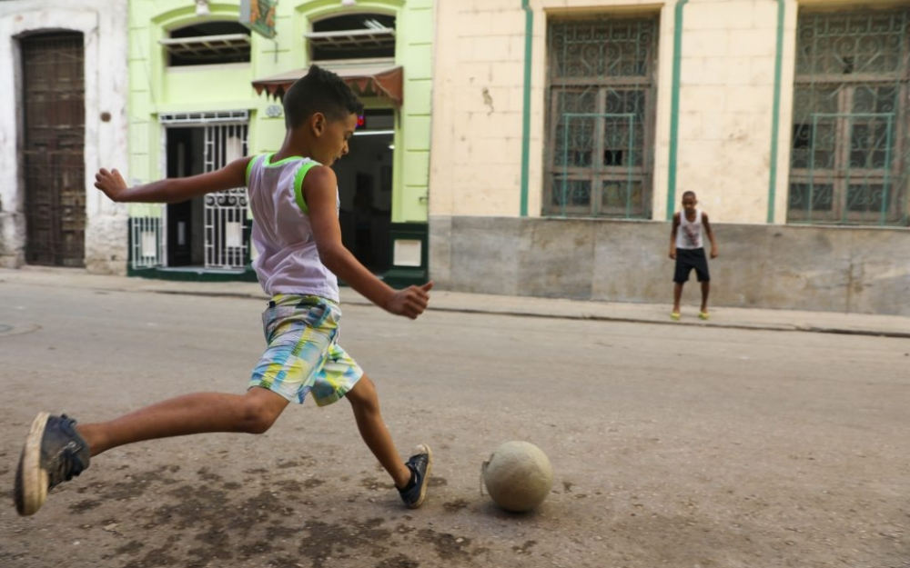 A boy playing soccer in the streets in Havana, Cuba Luke Galati Photography