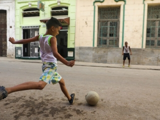 A boy playing soccer in the streets in Havana, Cuba Luke Galati Photography