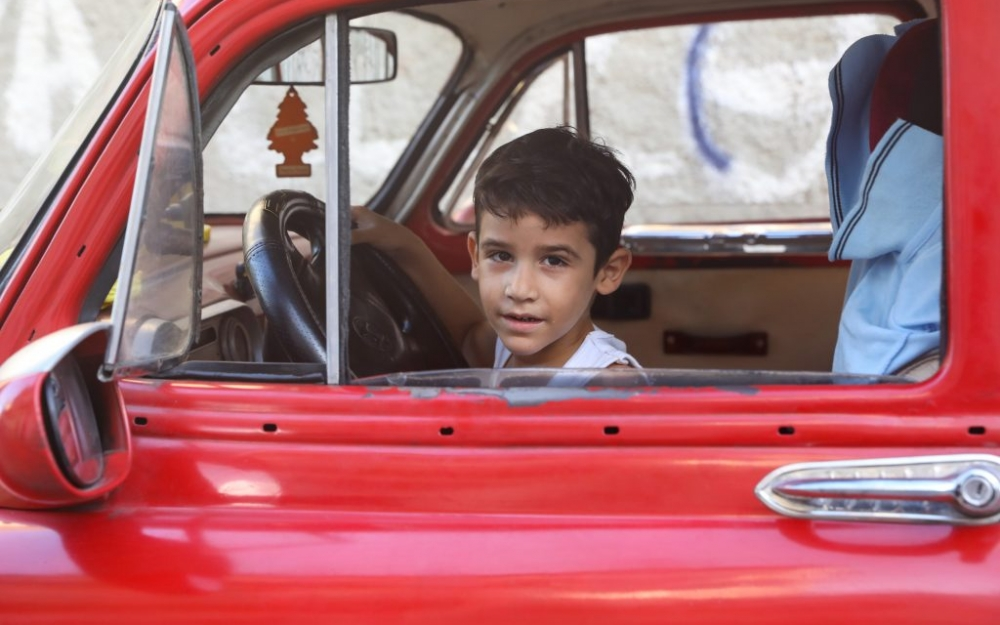 A boy in the driver's seat of a red car in Havana, Cuba by Luke Galati