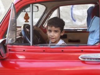 A boy in the driver's seat of a red car in Havana, Cuba by Luke Galati