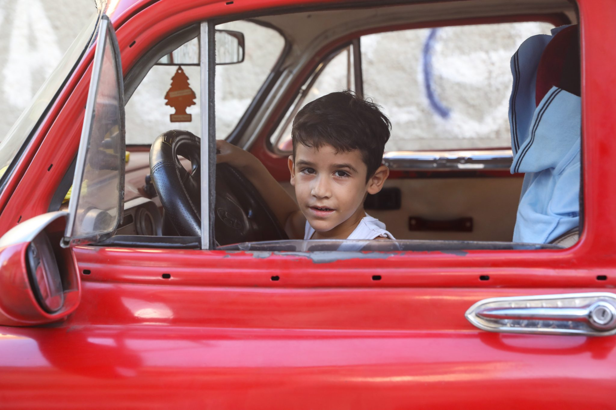 A boy in a red car in Central Havana. Photography by Luke Galati/2016