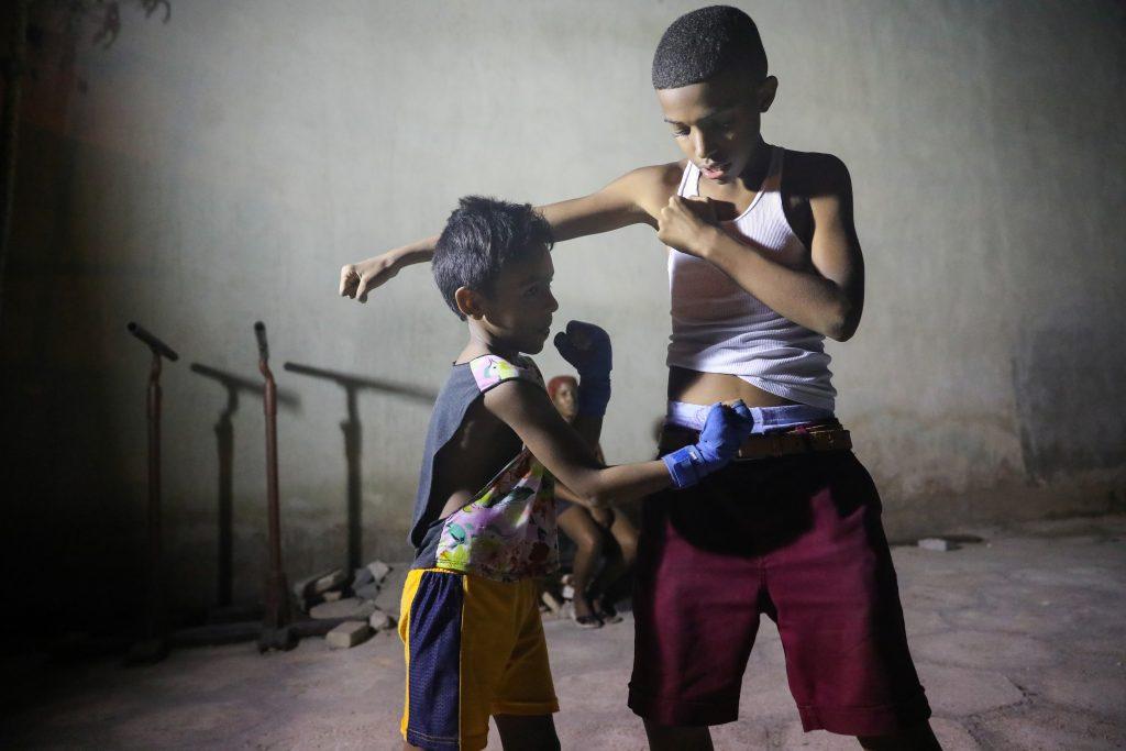 Two boys shadow box in Central Havana's Gimnasio de Boxeo Centro Habana. Luke Galati Photography