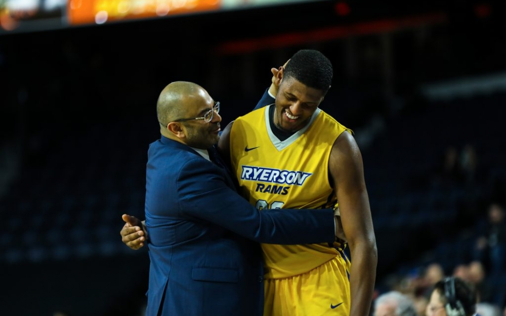 Ryerson forward, Juwon Grannnum walks off of the court as a Ram for the final time, as coach Roy Rana embraces him. Shot by Luke Galati/The Ryersonian
