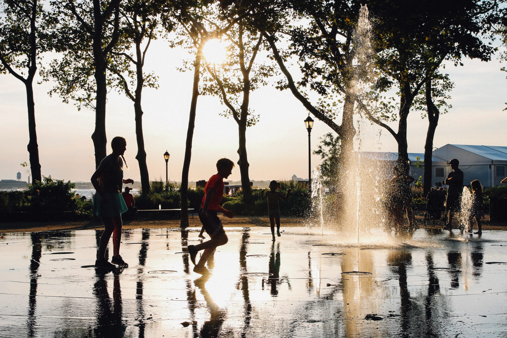 Children play in the water fountain at Battery Park. Luke Galati Photography in New York City