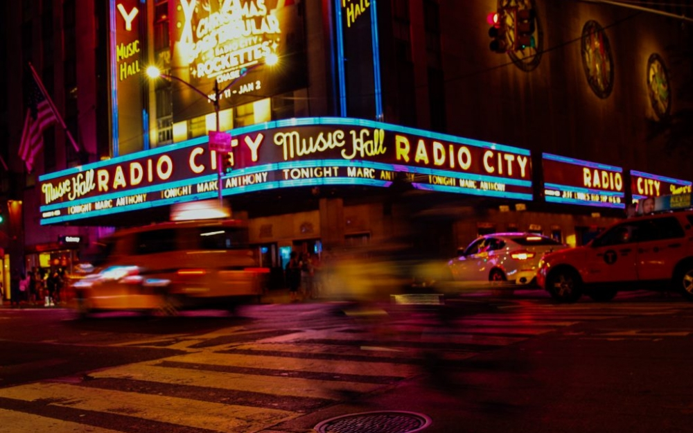 Radio City Music Hall as a cyclist passes by. Photo by Luke Galati in New York City