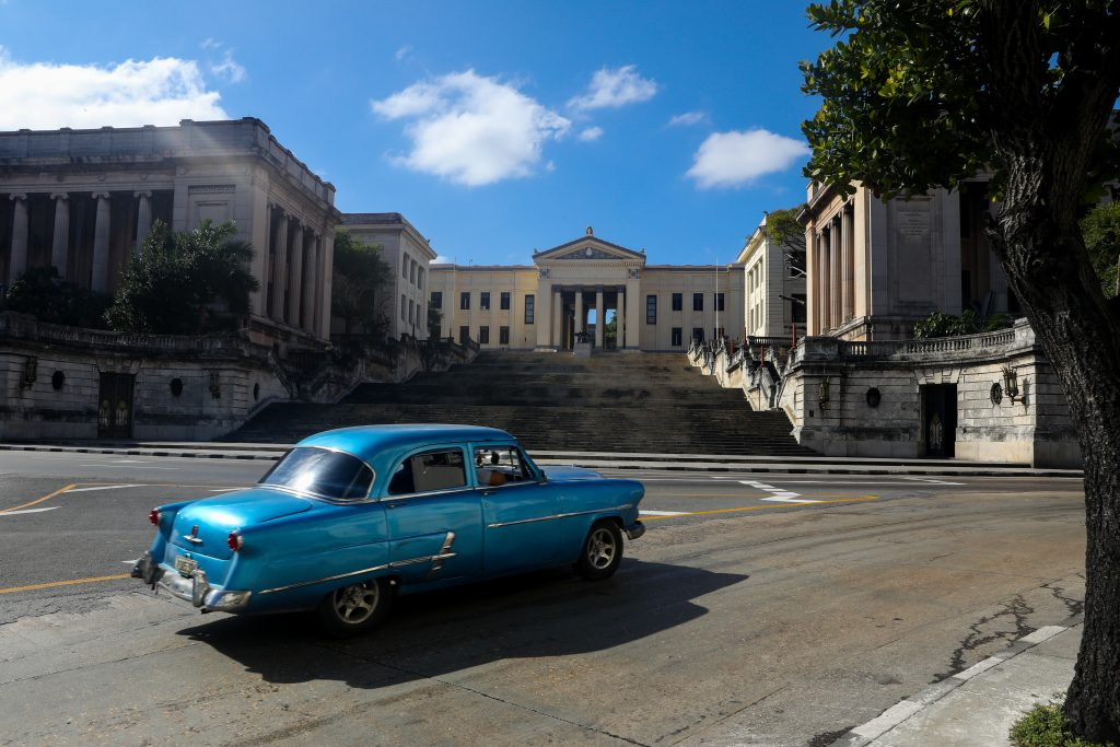 The stairs of the University of Havana, as a blue retro car passes by. Photo by Luke Galati in Cuba.