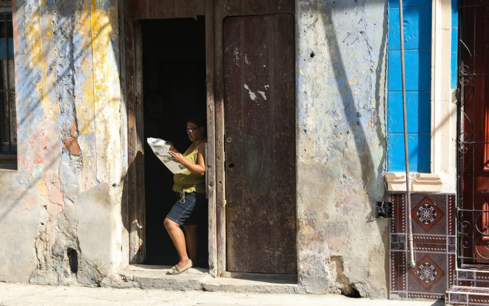 A woman reads a newspaper in Centro Havaba, Cuba. Luke Galati Photography in Havana, 2017