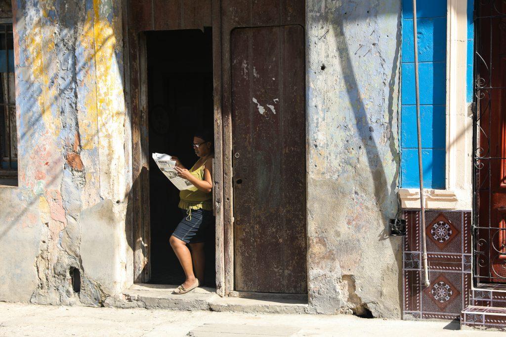 A woman reads a newspaper in Centro Havaba, Cuba. Luke Galati Photography in Havana, 2017