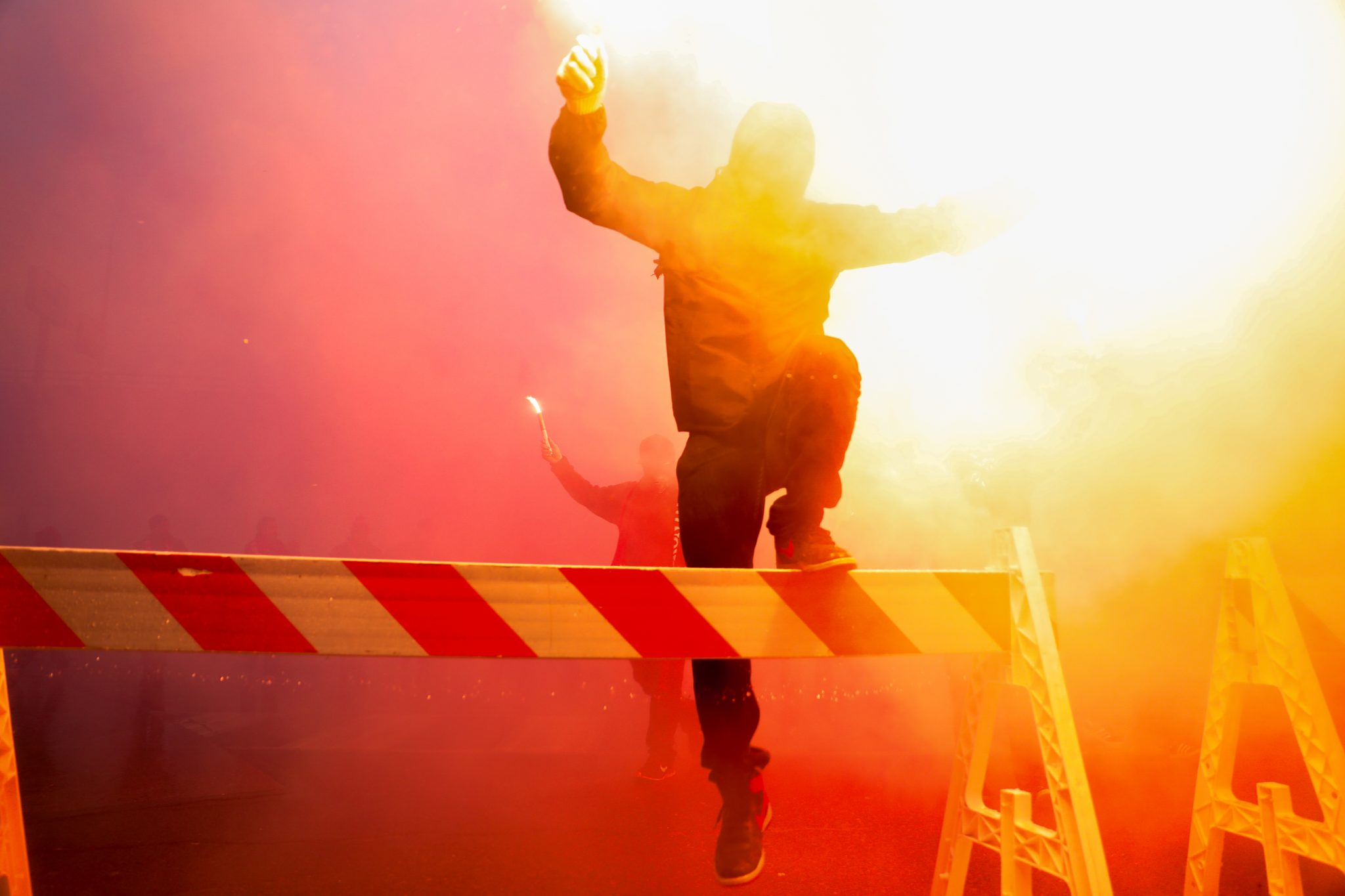 A Toronto FC fan with flares climbs over a barrier to the 2017 home opener at BMO Field. Luke Galati Photography/Toronto FC